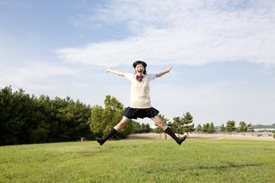 草原で元気よくジャンプする女子高校生の写真素材 [FYI00471439]