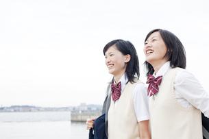 海沿いを歩く女子高校生二人の写真素材 [FYI00471446]