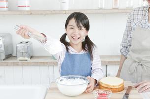 泡立て器についたクリームを見せる女の子の写真素材 [FYI00471546]