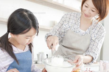 キッチンで泡立て器でホイップクリームを作っている女の子と母親の写真素材 [FYI00471553]