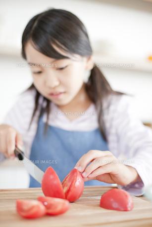 まな板の上でトマトを切る女の子の素材 [FYI00471557]