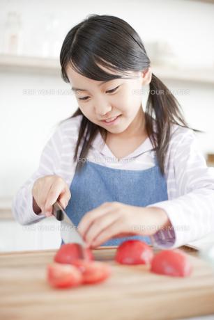 まな板の上でトマトを切る女の子の素材 [FYI00471559]