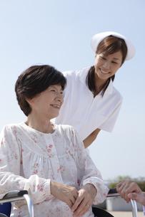 青空と車椅子の笑顔のシニア女性と女性看護師の写真素材 [FYI00471567]