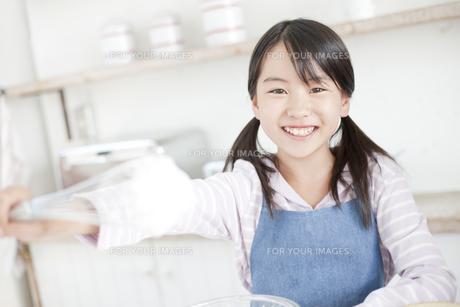 泡立て器を差し出す笑顔の女の子の写真素材 [FYI00471572]