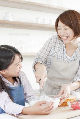 キッチンで泡立て器でホイップクリームを作っている女の子と母親の写真素材 [FYI00471574]