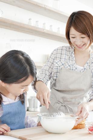 キッチンで泡立て器でホイップクリームを作っている女の子と母親の写真素材 [FYI00471575]