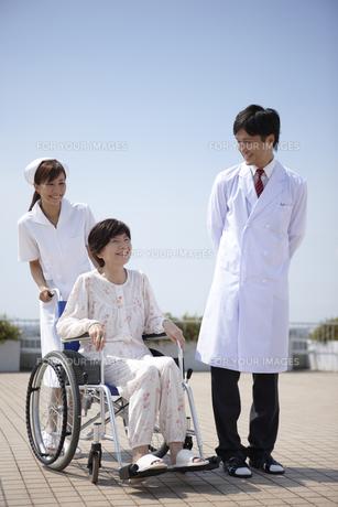 青空と車椅子の笑顔のシニア女性と女性看護師と医師の写真素材 [FYI00471576]