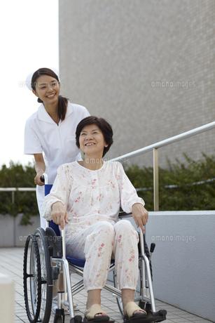 病院の玄関でシニア女性の乗った車椅子を押す女性看護師の写真素材 [FYI00471600]