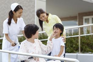 車椅子に乗ったシニア女性と話をする笑顔の女性と男の子の写真素材 [FYI00471614]