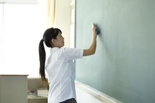 黒板に書いた文字を消している女子高生の写真素材 [FYI00471631]