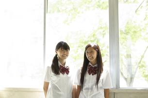教室の窓際に立つ笑顔の女子高生二人の写真素材 [FYI00471645]