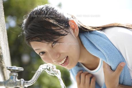 蛇口から出る水を顔に浴びる白いTシャツの女子高生の写真素材 [FYI00471664]