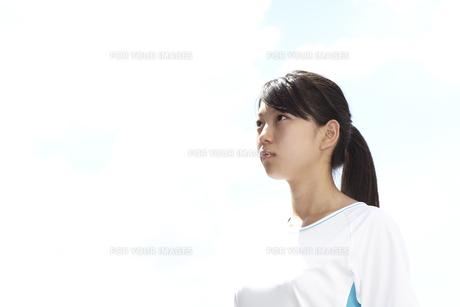 青空の下で遠くを見つめる白いTシャツの女子高生の写真素材 [FYI00471672]