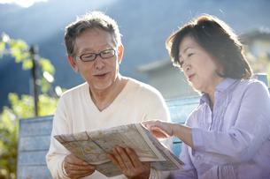田舎町の駅のホームのベンチに座り地図を見ているシニア夫婦の写真素材 [FYI00471679]