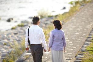 夕暮れの川岸の石畳の歩道を歩くシニア夫婦の後姿の写真素材 [FYI00471704]