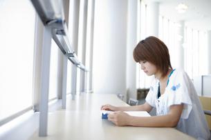 大学の図書館の窓際の席で読書する女子大生の写真素材 [FYI00471743]