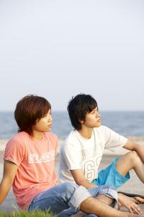 海辺に座り夕日を見ている若者二人の写真素材 [FYI00471749]