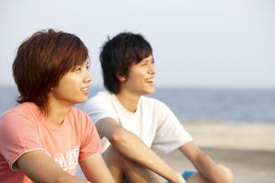 海辺に座り夕日を見ている笑顔の若者二人の写真素材 [FYI00471752]