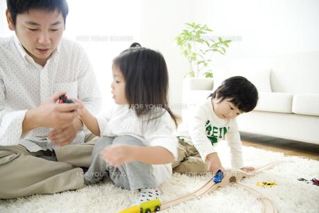 車のおもちゃで遊ぶ女の子とお父さんと男の子の写真素材 [FYI00471958]
