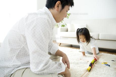 車のおもちゃで遊ぶ女の子とお父さんの写真素材 [FYI00471961]