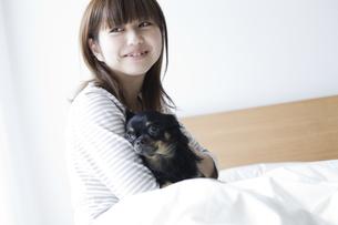 ベットでくつろぐ女性と犬の写真素材 [FYI00471966]