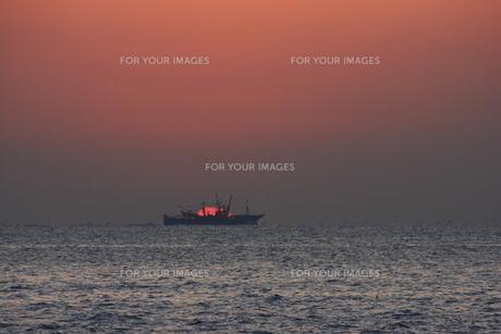 日の出の海と貨物船の写真素材 [FYI00473870]
