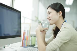 コーヒーを飲みながらパソコンを閲覧するビジネスウーマンの写真素材 [FYI00474119]