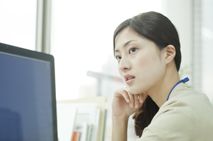 パソコンの前で頬杖をするビジネスウーマンの写真素材 [FYI00474125]