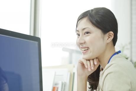 パソコンの前で頬杖をする笑顔のビジネスウーマンの写真素材 [FYI00474131]