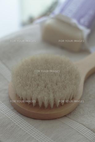 タオルの上に置いたボディブラシと石鹸の写真素材 [FYI00474233]