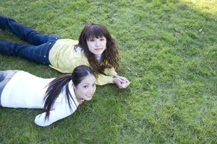 芝の上に横たわる学生の写真素材 [FYI00476540]