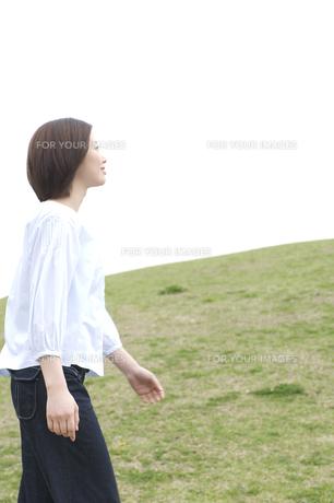 芝生の上を歩く女性の写真素材 [FYI00476578]