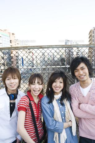 フェンスの前で笑う若者たちの写真素材 [FYI00478021]