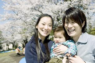 桜の木下で微笑むファミリーの写真素材 [FYI00478042]