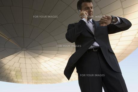 電話の最中に腕時計を見るビジネスマンの写真素材 [FYI00478048]