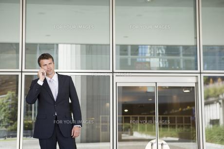ビルの入り口で携帯電話をかける男性の写真素材 [FYI00478059]