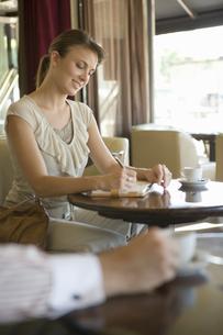 カフェでメモを取る女性の写真素材 [FYI00478065]