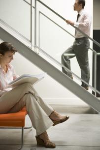 階段を上る男性と椅子に座る女性の写真素材 [FYI00478082]