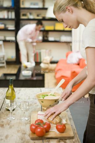 料理をする女性と犬と遊ぶ男性の写真素材 [FYI00478118]