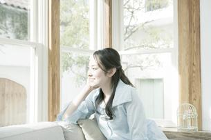 窓辺で頬杖をつく女性の写真素材 [FYI00478221]