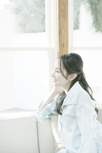 窓辺で頬杖をつく女性の写真素材 [FYI00478230]