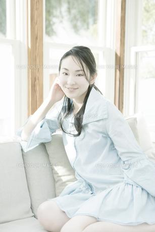 ソファに座り微笑む女性の写真素材 [FYI00478238]