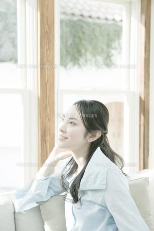 窓辺で頬杖をつく女性の写真素材 [FYI00478243]