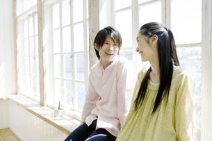 窓辺に座り見つめあうカップルの写真素材 [FYI00478336]