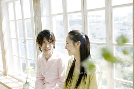 窓辺に座り微笑むカップルの写真素材 [FYI00478344]