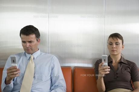 ソファに座り携帯電話を見る男女の写真素材 [FYI00478428]