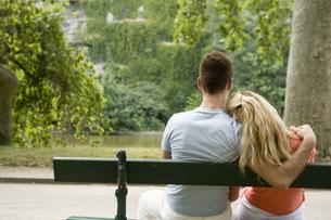 ベンチで肩を寄せ合うカップルの写真素材 [FYI00478443]