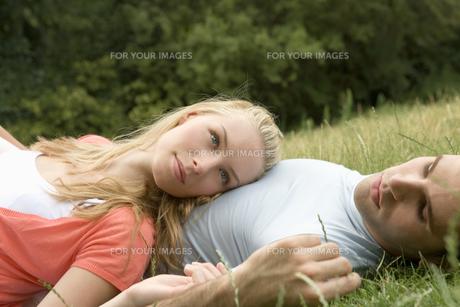 芝生で寝そべるカップルの写真素材 [FYI00478494]