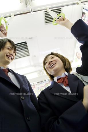 電車のつり革につかまり会話をする高校生の写真素材 [FYI00479840]