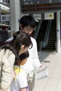 駅のホームで時刻表を見ている家族の写真素材 [FYI00479872]